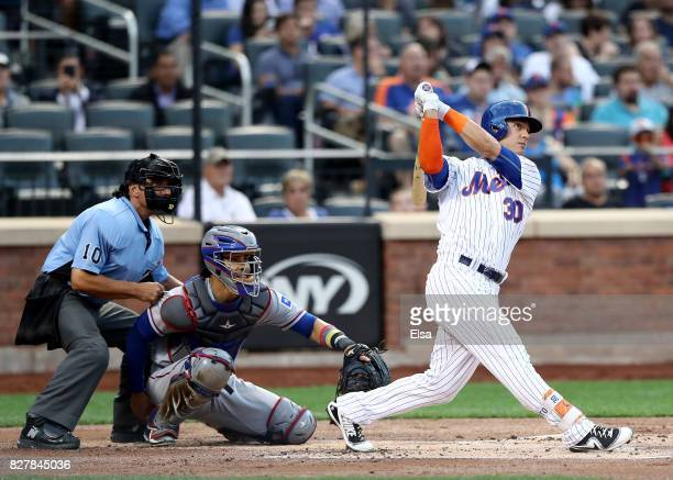 Michael Conforto of the New York Mets hits a solo home run as Robinson Chirinos of the Texas Rangers defends during interleague play on August 8 2017...
