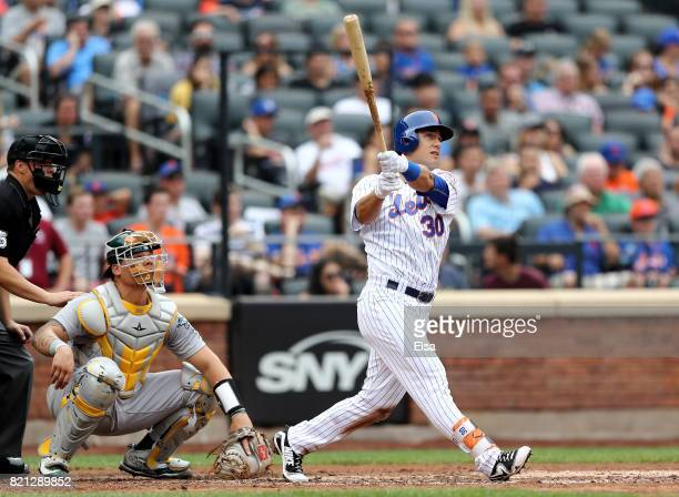 Michael Conforto of the New York Mets hits a solo home run in the third inning as Bruce Maxwell of the Oakland Athletics defends in the third inning...