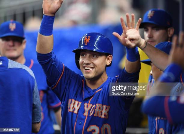 Michael Conforto of the New York Mets is congratulated by teammates after scoring a first inning run against the Atlanta Braves at SunTrust Field on...