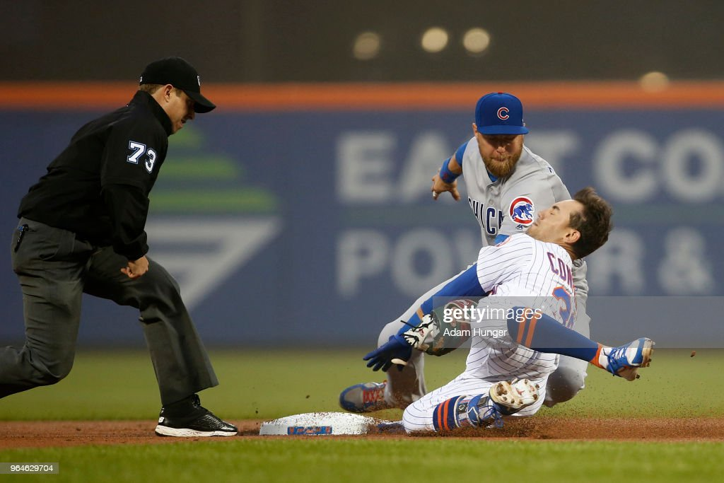 Michael Conforto #30 of the New York Mets is tagged out attempting to stretch a single into a double by Ben Zobrist #18 of the Chicago Cubs in front of umpire Tripp Gibson #73 during the second inning at Citi Field on May 31, 2018 in the Flushing neighborhood of the Queens borough of New York City.