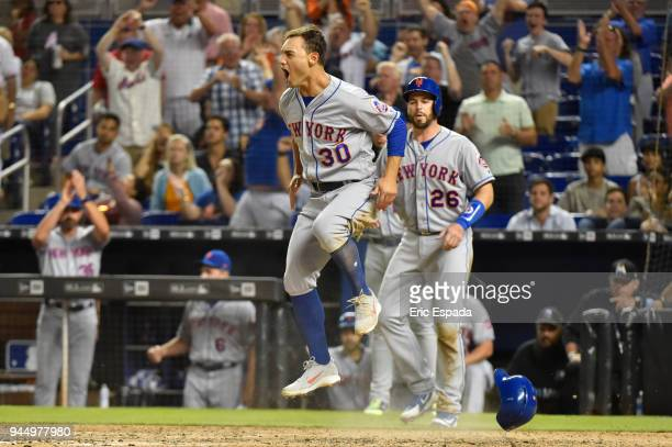 Michael Conforto of the New York Mets jumps in the air after scoring the go ahead run in the eighth inning against the Miami Marlins at Marlins Park...