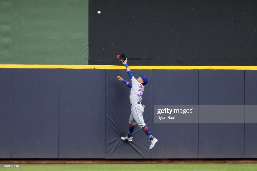 Michael Conforto #30 of the New York Mets looks on as a home run hit by Travis Shaw #21 of the Milwaukee Brewers clears the fence in the second inning at Miller Park on May 25, 2018 in Milwaukee, Wisconsin.