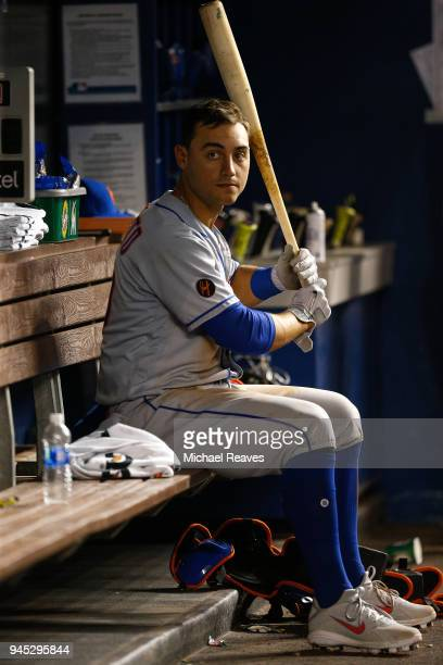 Michael Conforto of the New York Mets looks on in the dugout against the Miami Marlins at Marlins Park on April 9 2018 in Miami Florida