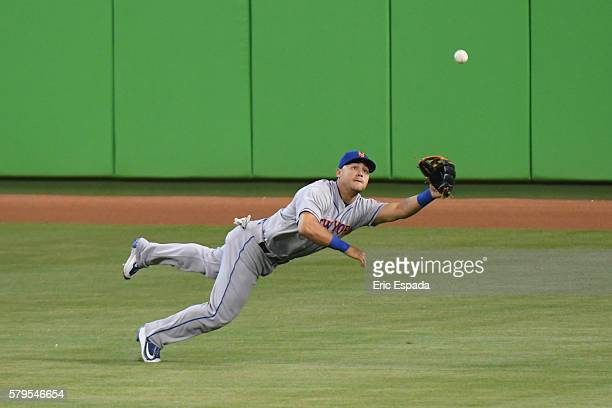 Michael Conforto of the New York Mets makes a diving catch in the first inning of the game against the Miami Marlins at Marlins Park on July 24 2016...