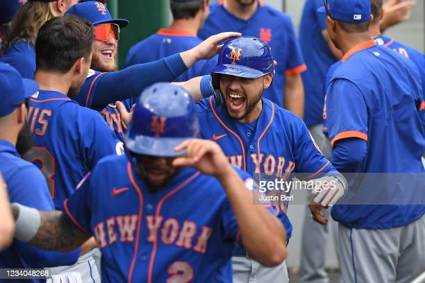 Michael Conforto of the New York Mets reacts in the dugout with teammates after hitting a two run home run in the ninth inning during the game...