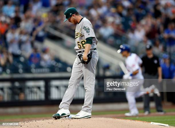 Michael Conforto of the New York Mets runs the bases in the background as pitcher Paul Blackburn of the Oakland Athletics reacts on the mound during...
