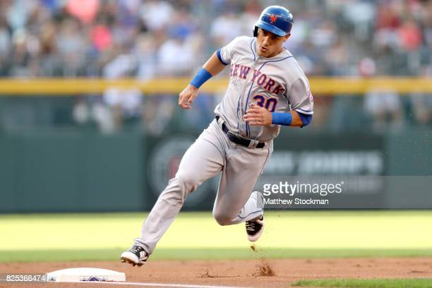 Michael Conforto of the New York Mets scores on a Yoenis Cespedes double in the first inning agaoinst the Colorado Rockies at Coors Field on August 1...