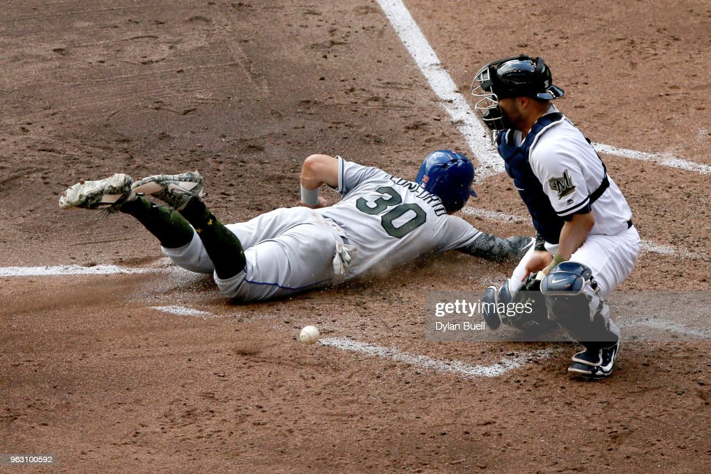 Michael Conforto #30 of the New York Mets slides into home plate to score a run past Manny Pina #9 of the Milwaukee Brewers in the fifth inning at Miller Park on May 27, 2018 in Milwaukee, Wisconsin.