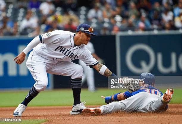 Michael Conforto of the New York Mets steals second base ahead of the tag of Manny Machado of the San Diego Padres during the seventh inning of a...