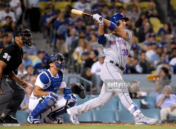 Michael Conforto of the New York Mets watches his two run homerun in front of Austin Barnes of the Los Angeles Dodgers to take a 40 lead during the...