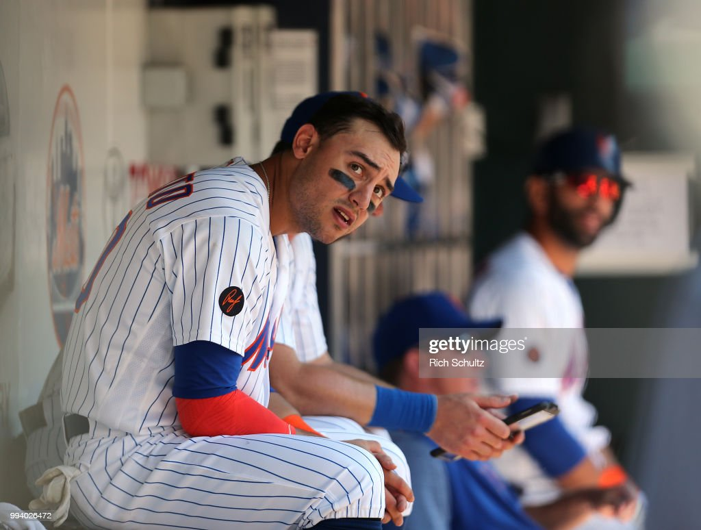 Michael Conforto #30 of the New York Mets watches the ninth inning from the dugout during a game against the Tampa Bay Rays at Citi Field on July 8, 2018 in the Flushing neighborhood of the Queens borough of New York City. The Rays defeated the Mets 9-0.