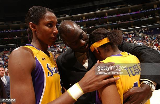 Michael Cooper consoles Nikki Teasley and Lisa Leslie after his last home game as head coach of the Los Angeles Sparks against the Phoenix Mercury at...