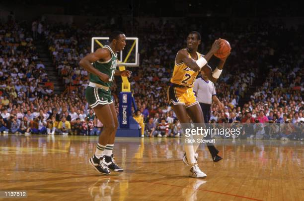 Michael Cooper of the Los Angeles Lakers holds the ball during an NBA game against the Boston Celtics at the Great Western Forum in Los Angeles,...