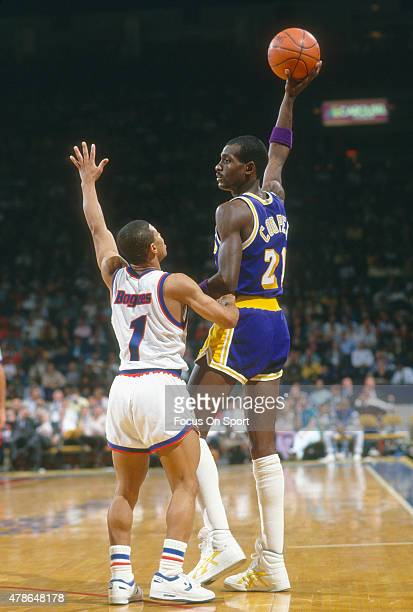 Michael Cooper of the Los Angeles Lakers looks to pass over the top of Muggsy Bogues of the Washington Bullets during an NBA basketball game circa...