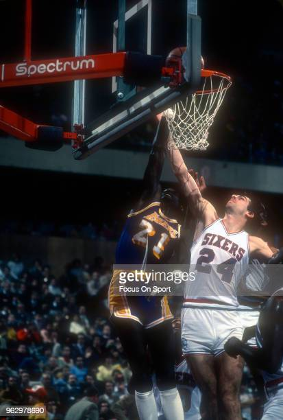Michael Cooper of the Los Angeles Lakers shoots over Bobby Jones of the Philadelphia 76ers during an NBA basketball game circa 1988 at The Spectrum...