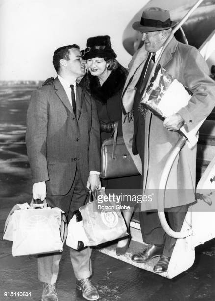 Michael 'Corky' Cronin left kisses his mother on the cheek as his parents Mrs and Mr Joe Cronin arrive at Logan Airport after a trip