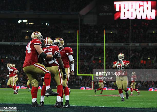 Michael Crabtree of San Francisco 49ers is congratulated by team mates as he scores their second touchdown during the NFL International Series match...