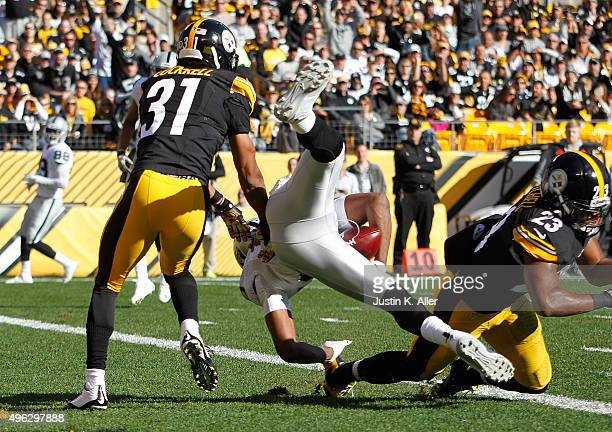 Michael Crabtree of the Oakland Raiders catches a 22yard touchdown pass from Derek Carr in between Ross Cockrell and Mike Mitchell of the Pittsburgh...