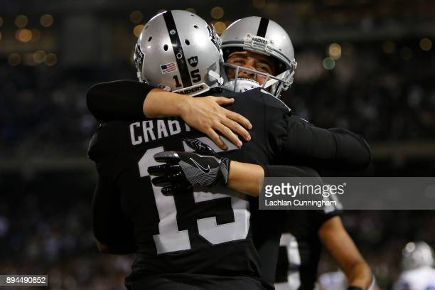 Michael Crabtree of the Oakland Raiders celebrates with Derek Carr after a twoyard touchdown catch against the Dallas Cowboys during their NFL game...