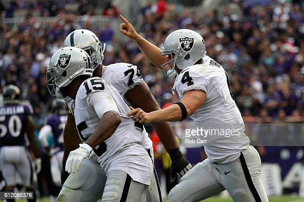 Michael Crabtree of the Oakland Raiders celebrates with Derek Carr after catching a touchdown pass against the Baltimore Ravens at MT Bank Stadium on...