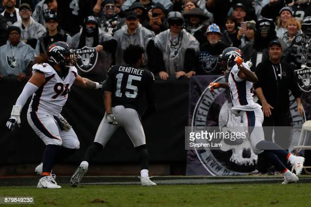 Michael Crabtree of the Oakland Raiders fights with Aqib Talib of the Denver Broncos during the first quarter their NFL football game at...