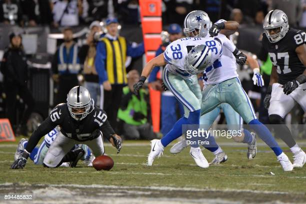 Michael Crabtree of the Oakland Raiders fumbles the ball during their NFL game against the Dallas Cowboys at OaklandAlameda County Coliseum on...
