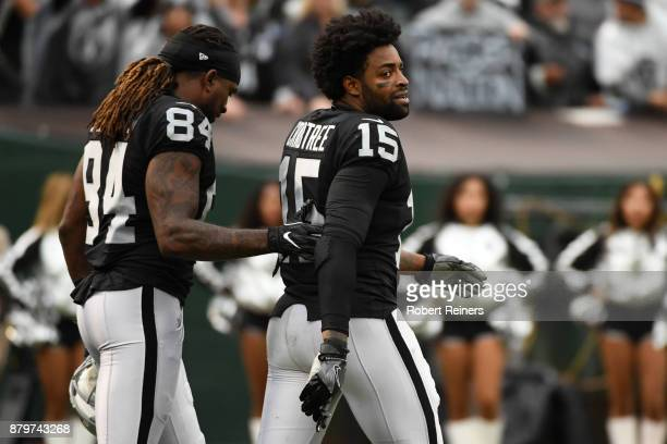 Michael Crabtree of the Oakland Raiders is walked off the field by Cordarrelle Patterson after being ejected for fighting with Aqib Talib of the...