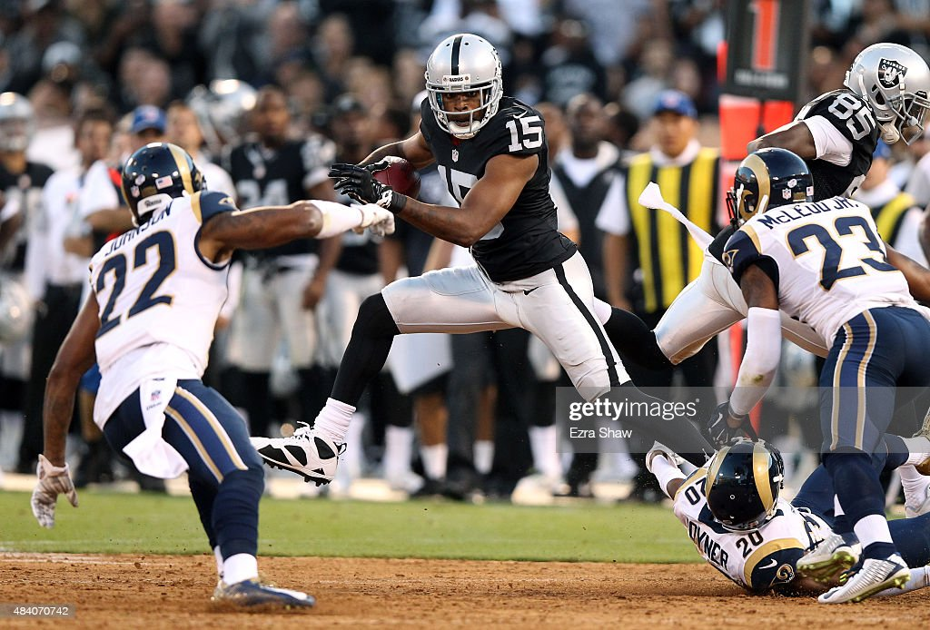 Michael Crabtree #15 of the Oakland Raiders tries to avoid being tackled by Lamarcus Joyner #20 and Trumaine Johnson #22 of the St. Louis Rams at O.co Coliseum on August 14, 2015 in Oakland, California.