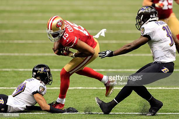 Michael Crabtree of the San Francisco 49ers breaks tackles against Cary Williams and Bernard Pollard of the Baltimore Ravens and runs in for a...