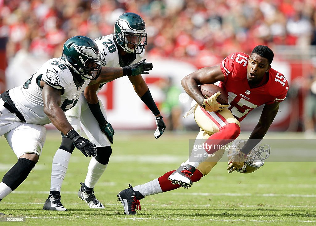 Michael Crabtree #15 of the San Francisco 49ers runs away from Trent Cole #58 and Cary Williams #26 of the Philadelphia Eagles after Williams pulled Crabree's helmet off in the second quarter of their game at Levi's Stadium on September 28, 2014 in Santa Clara, California.
