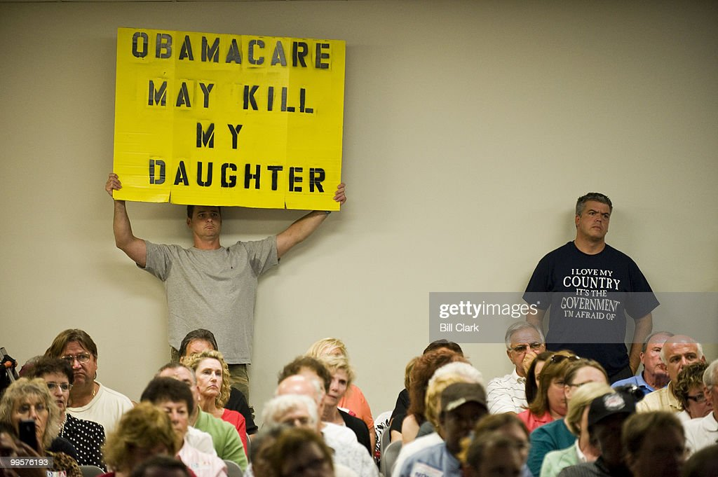 Michael Craig, left, of Middletown, N.J., holds up a sign opposing Obamacare during Rep. Frank Pallone's town hall meeting at Red Bank Middle School in Red Bank, N.j., on Tuesday evening, Aug. 25, 2009. Craig says he fears bureaucrats will make medical decisions for his daughter instead of her doctor.