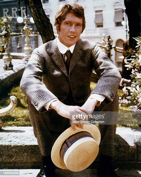 Michael Crawford British actor in wearing a grey check suit and holding a straw boater in a publicity portrait issued for the film 'Hello Dolly' 1969...