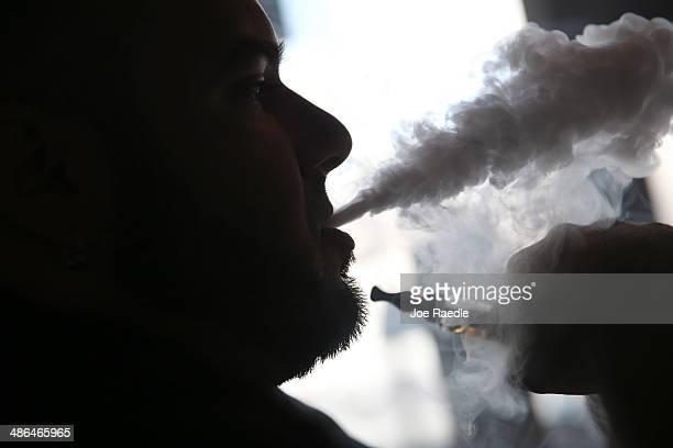 Michael Crespo a salesman waits for customers as he enjoys an electronic cigarette at the Vapor Shark store on April 24 2014 in Miami Florida Brandon...