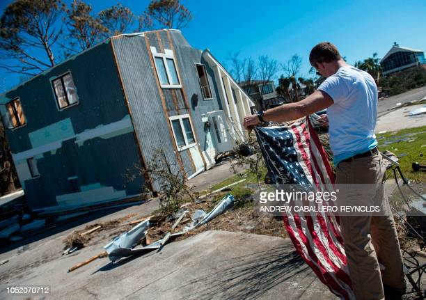 Michael Crossley picks up a US National flag from his home that was washed across the street in the background in Port St Joe beach Florida on...