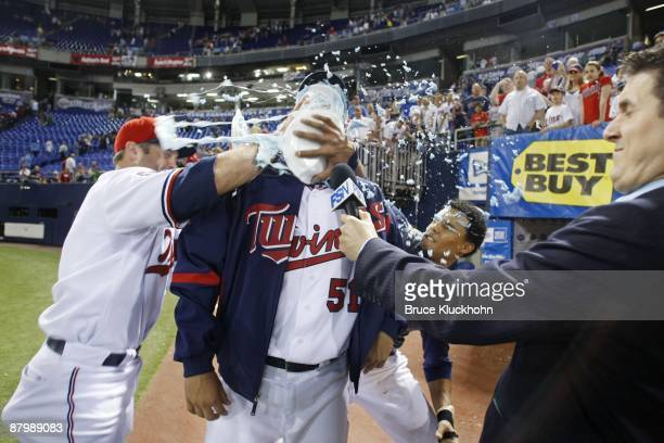 Michael Cuddyer and Carlos Gomez and Luis Ayala give Anthony Swarzak of the Minnesota Twins shaving cream pies to his face as he is interviewed by...