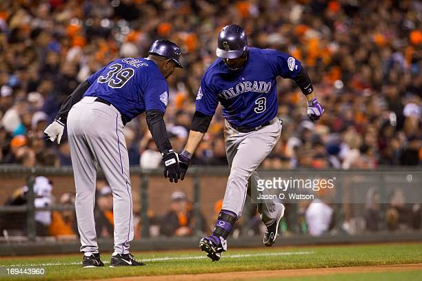 Michael Cuddyer of the Colorado Rockies is congratulated by third base coach Stu Cole after hitting a home run off of Tim Lincecum of the San...