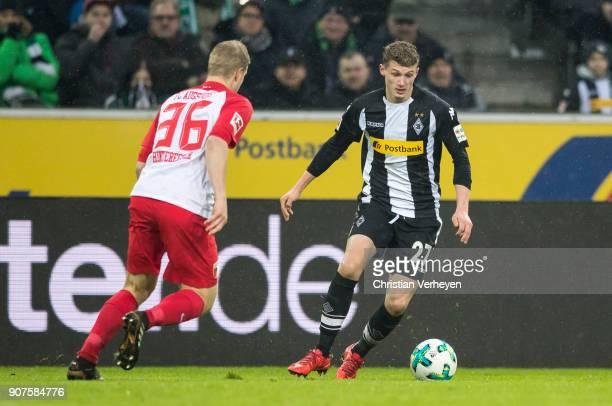 Michael Cuisance of Borussia Moenchengladbach and Martin Hinteregger of FC Augsburg battle for the ball during the Bundesliga match between Borussia...