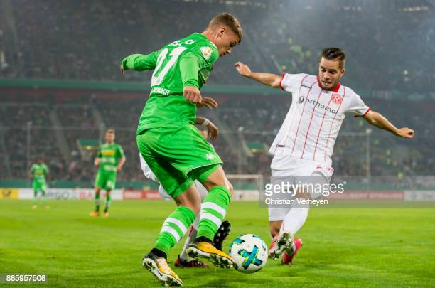 Michael Cuisance of Borussia Moenchengladbach and Niko Giesselmann of Fortuna Duesseldorf battle for the ball during the DFB Cup match between...