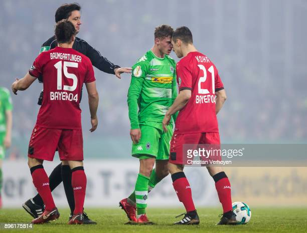 Michael Cuisance of Borussia Moenchengladbach bickers with Dominik Kohr of Bayer 04 Leverkusen during the DFBCup match between Borussia...