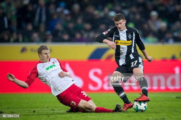 Michael Cuisance of Borussia Moenchengladbach is attacked by Martin Hinteregger of FC Augsburg during the Bundesliga match between Borussia...