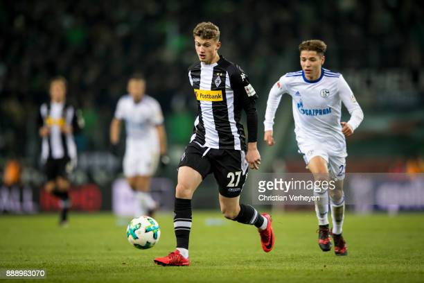 Michael Cuisance of Borussia Moenchengladbach is chased by Amine Harit of FC Schalke 04 during the Bundesliga match between Borussia Moenchengladbach...