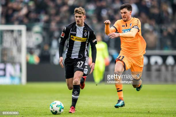 Michael Cuisance of Borussia Moenchengladbach is chased by Florian Grillitsch of 1899 Hoffenheim during the Bundesliga match between Borussia...