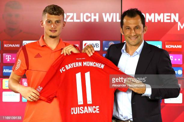 Michael Cuisance of FC Bayern Muenchen poses with sporting director Hasan Salihamidzic during a press conference at Bayern Muenchen's headquarters...