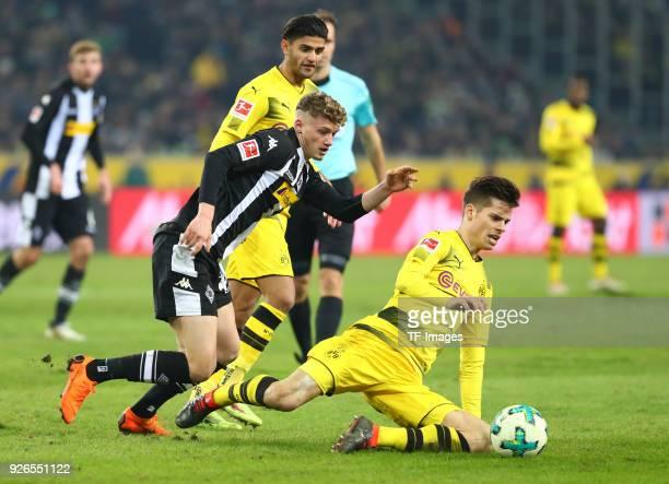 Michael Cuisance of Moenchengladbach and Julian Weigl of Dortmund battle for the ball during the Bundesliga match between Borussia Moenchengladbach...