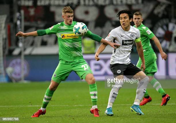 Michael Cuisance of Moenchengladbach and Makoto Hasebe of Frankfurt battle for the ball during the Bundesliga match between Eintracht Frankfurt and...