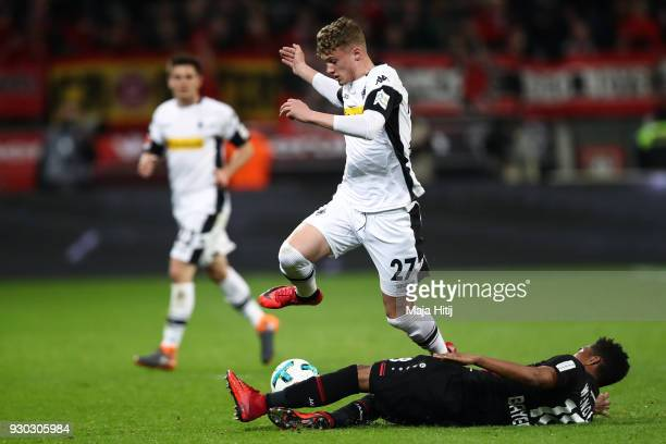 Michael Cuisance of Moenchengladbach and Wendell of Leverkusen battle for the ball during the Bundesliga match between Bayer 04 Leverkusen and...