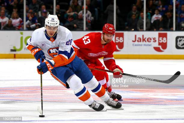 Michael Dal Colle of the New York Islanders is pursued by Darren Helm of the Detroit Red Wings during the first period at NYCB Live's Nassau Coliseum...