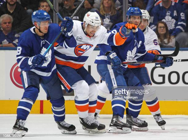 Michael Dal Colle of the New York Islanders tries to squeeze between Andreas Johnsson and John Tavares of the Toronto Maple Leafs during an NHL game...