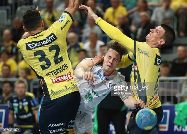 Michael Damgaard *C of Magdeburg is challenged by Alexander Petersson *L and Andy Schmid of RheinNeckar Loewen during the DKB HBL match between...