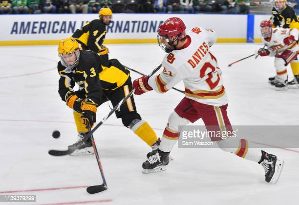Michael Davies of the Denver Pioneers shoots against Patrik Demel of the American International Yellow Jackets during the NCAA Division I Men's Ice...